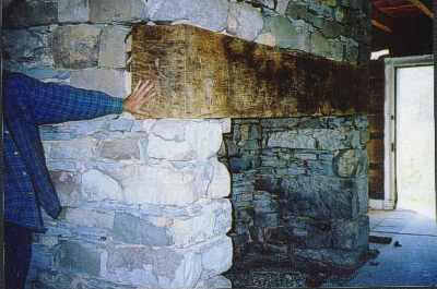 Very large limestone fireplace with big beam mantel.